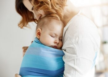 Precious little newborn boy having deep sleep at day on mother chest in blue baby slim. Mom kissing baby head and feeling relaxed and delight. Family concept
