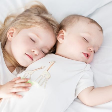 charming little brother and sister asleep embracing on white background